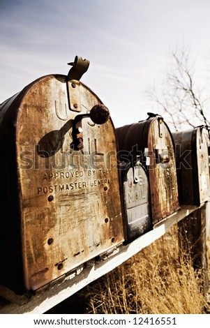 Old American mailboxes in late sun, rusting away in rural Midwest. - stock photo
