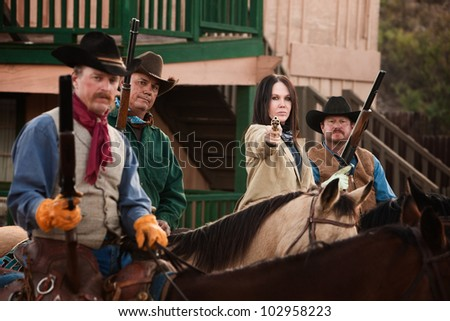 Old American west woman with pistol and 3 armed men - stock photo