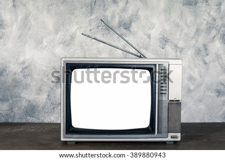 Old analogue television on wood table with textured background. - stock photo