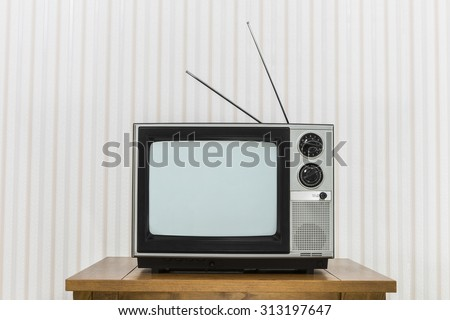 Old analogue television with antenna on wood table - stock photo