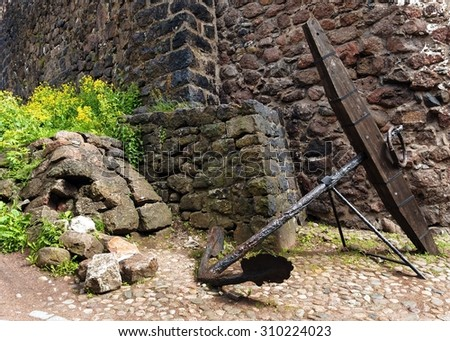 Old anchor on a background of the fortress wall - stock photo