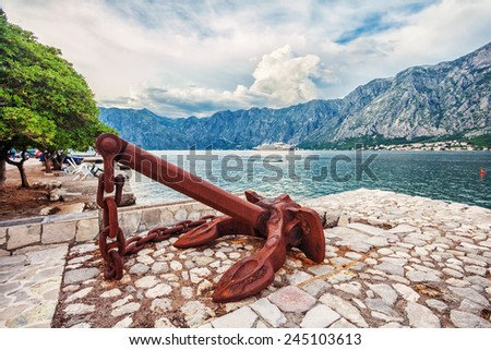 Old anchor on the waterfront on mountains background. Fish-eye view. Montenegro - stock photo