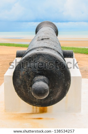 old ancient cannon gun aims across the harbour - stock photo