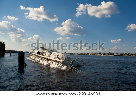 Old and abandoned passenger boat with damaged hull tied at dock half sinking in water - stock photo