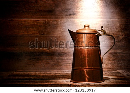 Old and antique vintage copper water pitcher or coffee pot with handcrafted brass handle on aged wood boards serving table in an ancient historic house - stock photo