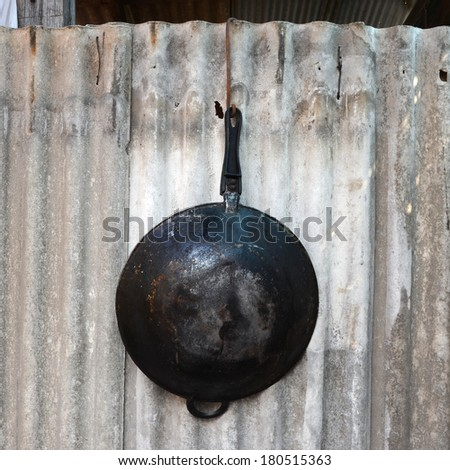 Old and black pans hanging on the wall. - stock photo