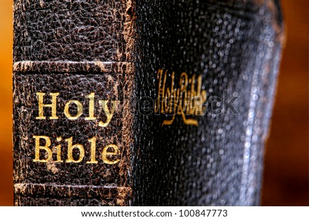 Old and damaged antique holy bible sacred religious book spine detail close up with vintage embossed gold lettering on worn binding - stock photo