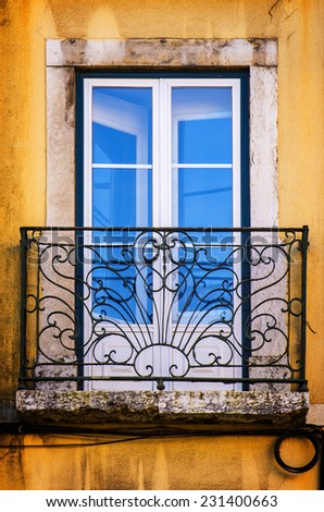 Old and damaged window with iron balcony in a yellow wall - stock photo