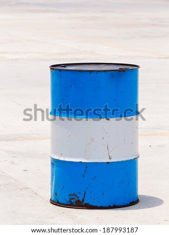 Old and dirty oil barrel tank isolated on concrete floor in bright sunlight - stock photo