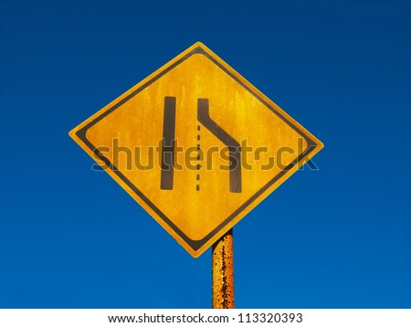 Old and grungy road narrows sign or lane merge sign against a deep blue  sky background. - stock photo