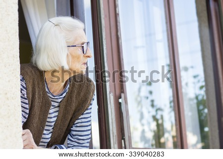 Old and lonely lady looking outside through her window - stock photo