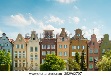 Old and narrow houses in street of Gdansk, Poland, Europe. Beautiful sunny day, colorful narrow buildings standing in row. - stock photo