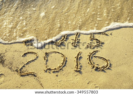 Old and new year written on the beach - stock photo