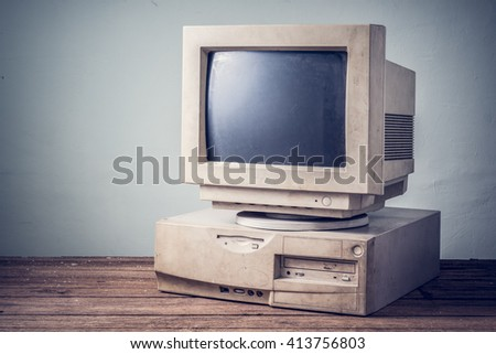 old and obsolete computer on old wood table with concrete wall background, vintage color tone - stock photo