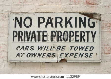 Old and rough no-parking sign on a brick wall - stock photo