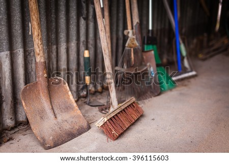 Old and rusted garden tools in an old garage - stock photo