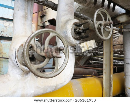 Old and rusty industrial pipe valve for hot water at power plant - stock photo