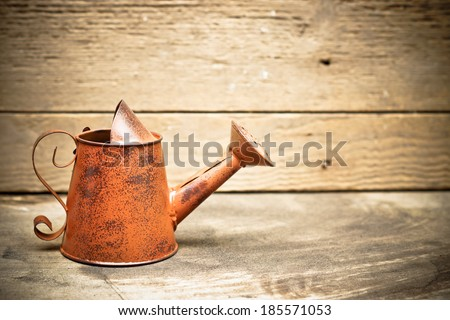 old and rusty watering can with wood background - stock photo