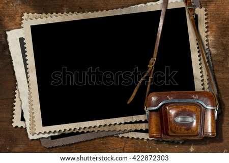 Old and vintage camera with leather case and a stack of old vintage photo frames on a wooden background - stock photo