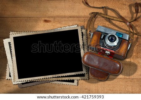 Old and vintage camera with leather case and a stack of photo frames on a wooden table - stock photo
