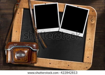 Old and vintage camera with leather case, two empty instant photo frames and a blank blackboard with wooden frame - stock photo