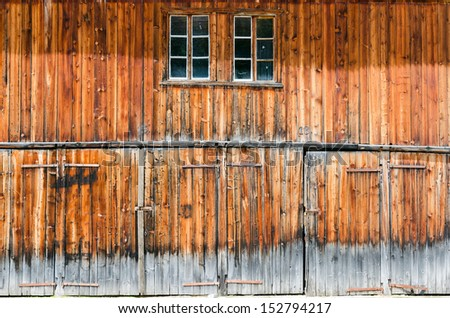 Old and weathered wooden barn facade in direct sunlight - stock photo
