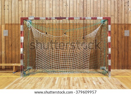 Old and worn soccer goalpost in old gymhall - stock photo