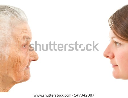 old and young faces up against each other on an isolted background - stock photo