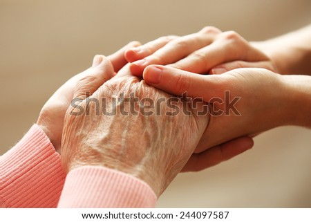 Old and young holding hands on light background - stock photo