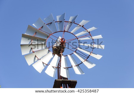 Old antique Aermotor windmill used to pump water and beautiful blue sky. - stock photo