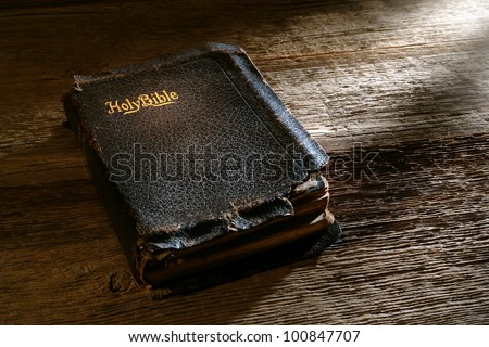 Old antique and damaged holy bible sacred religious book on weathered wood bench in a vintage church - stock photo