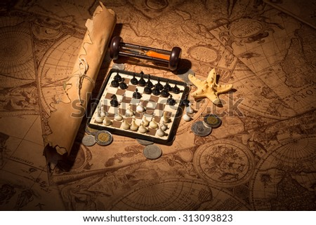 Old antique map with money and chess - stock photo