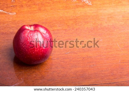 old apple on wooden background - stock photo