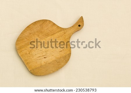 old apple shaped cutting board on fabric  - stock photo