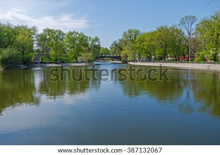 Old arch bridge is crossing the small pond of city park - stock photo