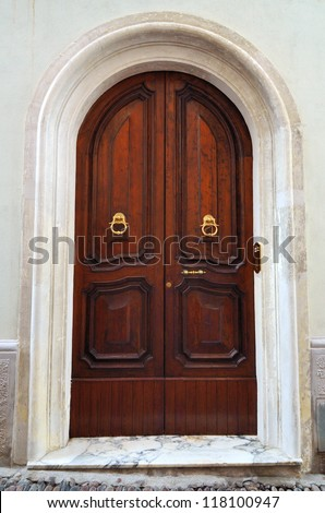 Old arch wooden door close-up - stock photo