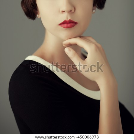 Old aristocracy concept. Close up portrait of posing young woman in black dress with her hand over gray background. Vintage hairdo. Studio shot - stock photo