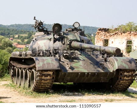 old army tank in front of ruins - stock photo
