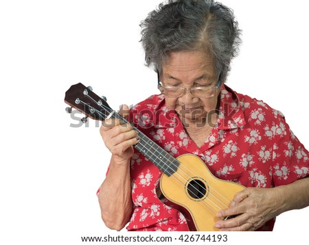 Old Asian Woman Playing The Ukulele - stock photo