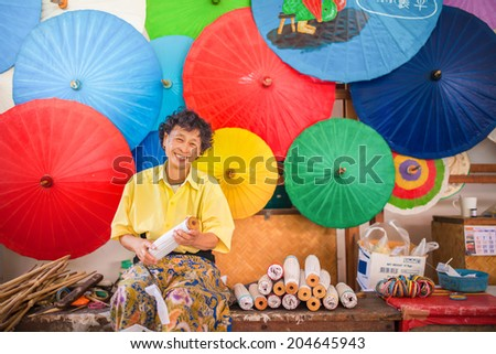old  asian Woman smiling, making a wooden umbrella in traditional umbrella factory,colorful umbrella background - stock photo