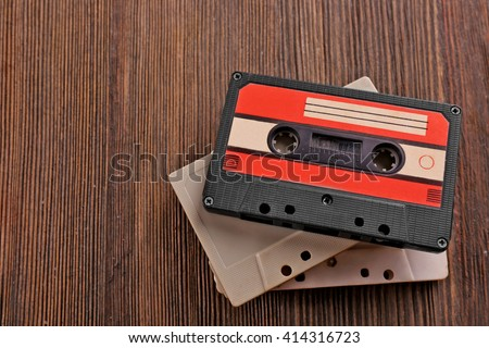 Old audio cassettes on wooden background - stock photo