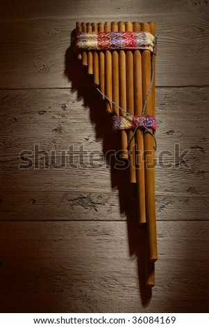 Old authentic panflute hanging on wood wall background - stock photo