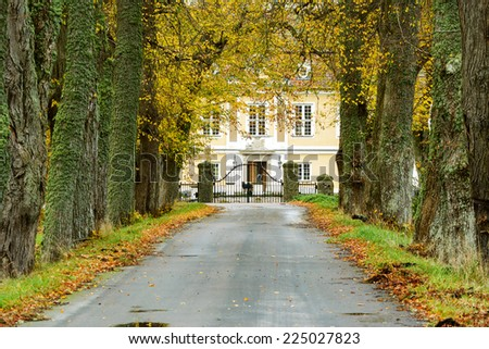 Old avenue in autumn leading up to gates of manor or small castle. - stock photo