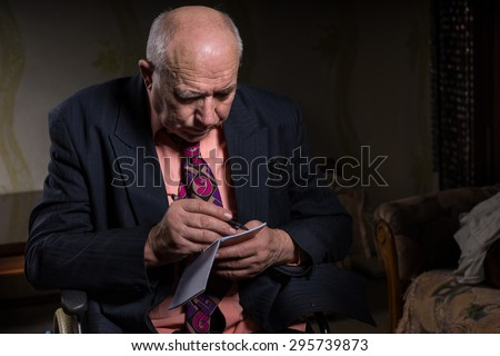 Old Bald Businessman in Formal Wear Sitting on his Wheelchair, Writing on his Small Notebook Seriously - stock photo