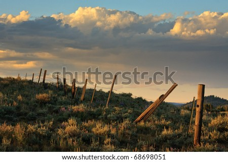 Old barb wire fence sitting atop a Montana hill at sunset. - stock photo