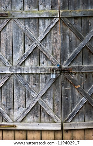 Old barn door with padlock - stock photo