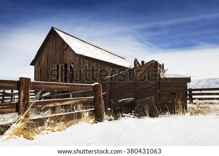 Old barn with fence in winter with snow. - stock photo