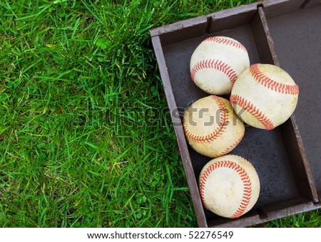 old baseballs in a wooden box on the field, copy space on grass at left - stock photo
