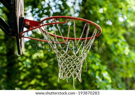 Old basketball hoop on green background  - stock photo