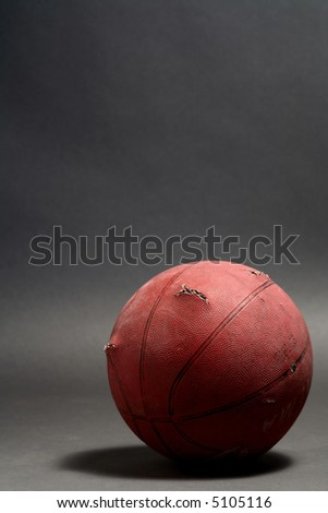 old basketball  resting on the gray floor - stock photo